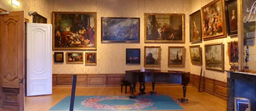 De salon van het Cromhouthuis met van onder tot boven schilderijen