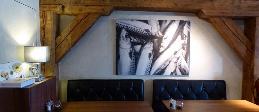 Foto's van vissen sieren de muur van restaurant 't Pakhuus