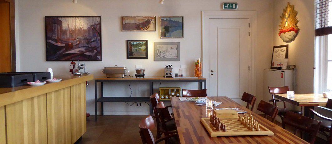 Schilderijen van stadsgezichten in de lounge van De oude stadsmuur verborgen in Kamer met bad en open haard in Comfort kamer van Hotel Corps de Garde
