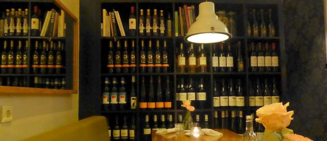 Een boekenkast met meer wijn dan kookboeken erin bij restaurant Voilà